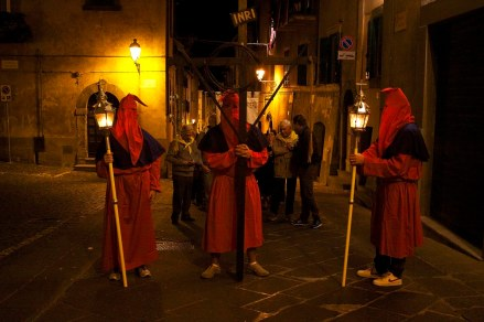 Cross and torch bearers lead the Processione di Santa Maria in Tuscania, Italy. (2013)