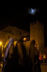 Nuns pass by the medieval walls of Tuscania during the annual tribute to St. Mary. Tuscania, Italy. (2013)