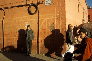 The man stands on a street corner in Marrakech, Morocco.