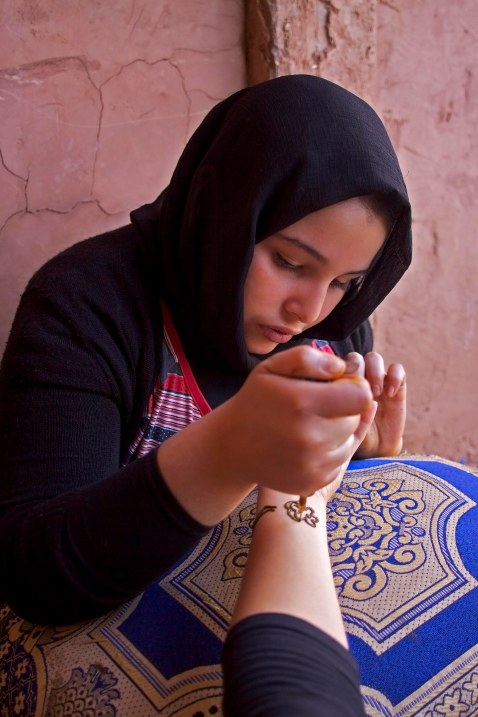 A young girl, a member of a local Berber family, applies henna at her home in the Ourika Valley. Marrakech, Morocco. (2013)