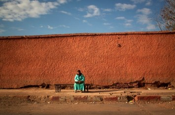 "A eoman sits in ""The New City,"" outside the median walls in Marrakech, Morocco. (2013)"