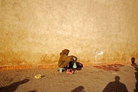 An old man sits near the Souk El Haddadine area inside the medina of Marrakech, Morocco.