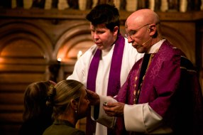 The Reverend Canon Robert Hendricks, left, and Dean Peter Eaton, right, impose ashes on the foreheads of worshipers at St. John's Cathedral in Denver, Colo. on Feb. 18, 2015. The ashes signify a devotion to Christ and lend the name to this particular service of Lent.