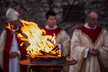 (L – R) The Right Reverend John Pritchard, The Reverend Canon Robert Hendrickson and The Reverend Canon Charles LaFond stand next to a ceremonial fire, a symbol of life for the church, prior to the Easter Vigil service on April 4, 2015 at St. John's Cathedral in Denver, Colo..