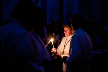 Bev Booth, an Acolyte, lights her candle during the Easter Vigil service at St. John's Cathedral on April 4, 2015. The ceremony begins in darkness, and with the entrance of the Paschal Candle, the individual candles of those in the congregation are lit from this single flame, resulting in a flickering crowd of glowing candles.
